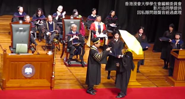 Estudiante de Hong Kong abre un paragua amarillo en su graduación