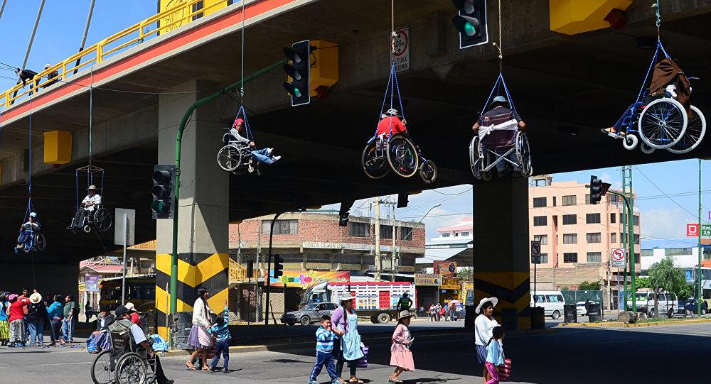 Bolivia: Se cuelgan de un puente con sus sillas de ruedas para exigir más recursos