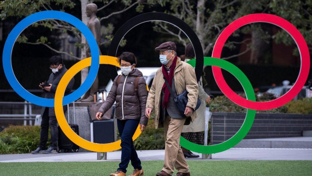 Habitantes de Japón con cubrebocas pasando por un monumento de los aros olímpicos