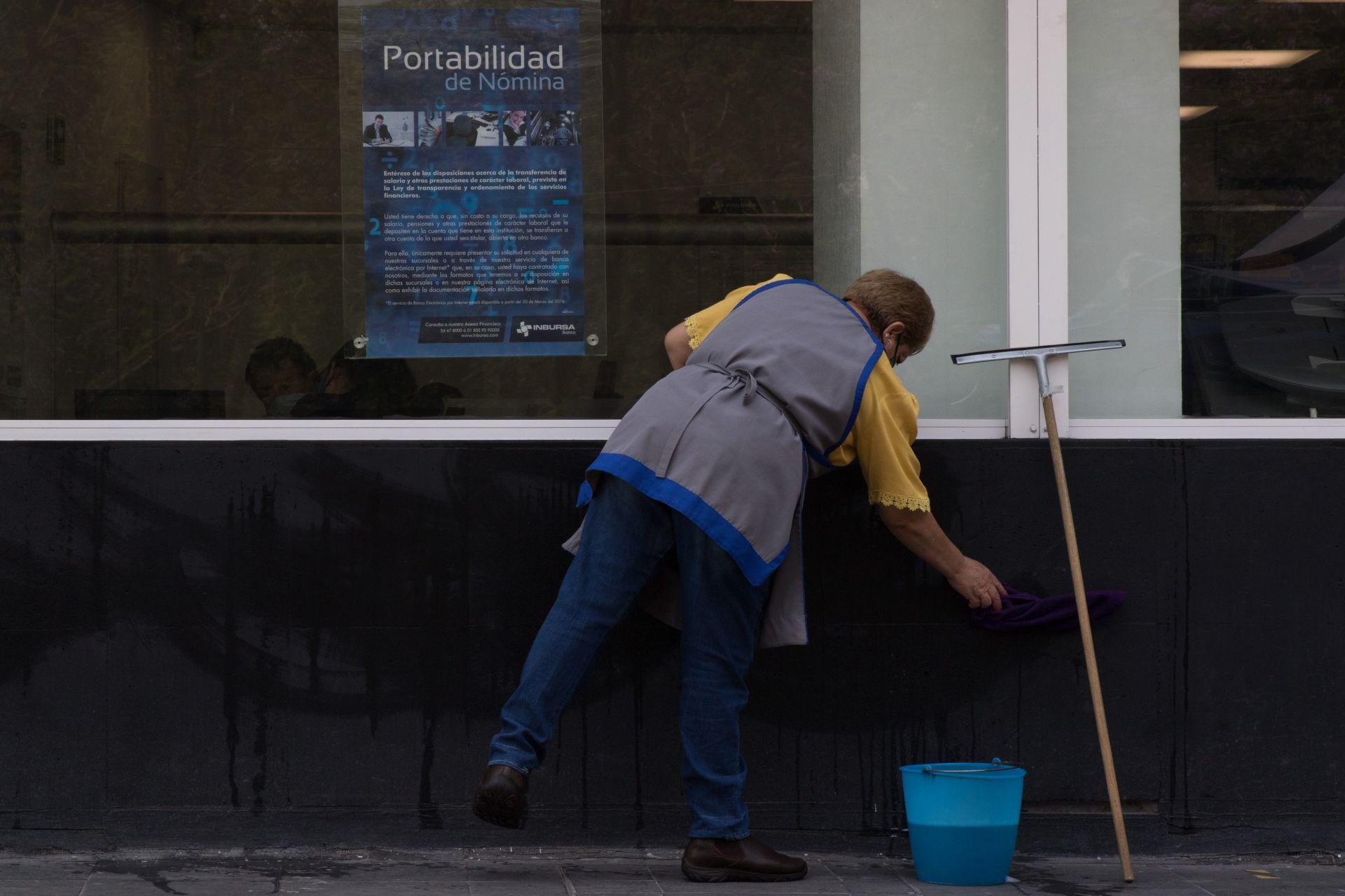 Trabajadora limpiando la parte de afuera de un banco