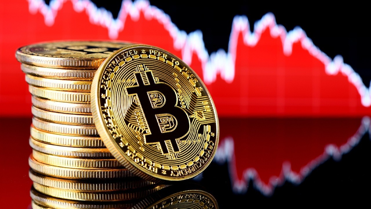 Se ven varias monedas de bitcoin apiladas en forma de columna y al fondo se ve una grafica de color roja