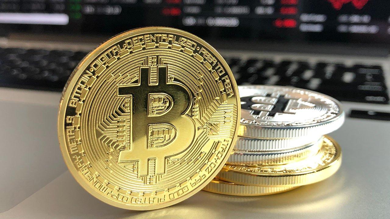 se ven unas pocas monedas de bitcoin encima de otras y una moneda aparte recargada sobre el montón