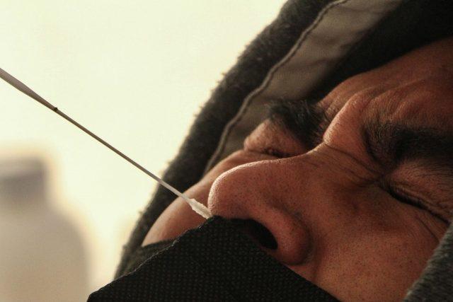 Adolescente aprieta los ojos durante toma nasal para la detección de coronavirus.