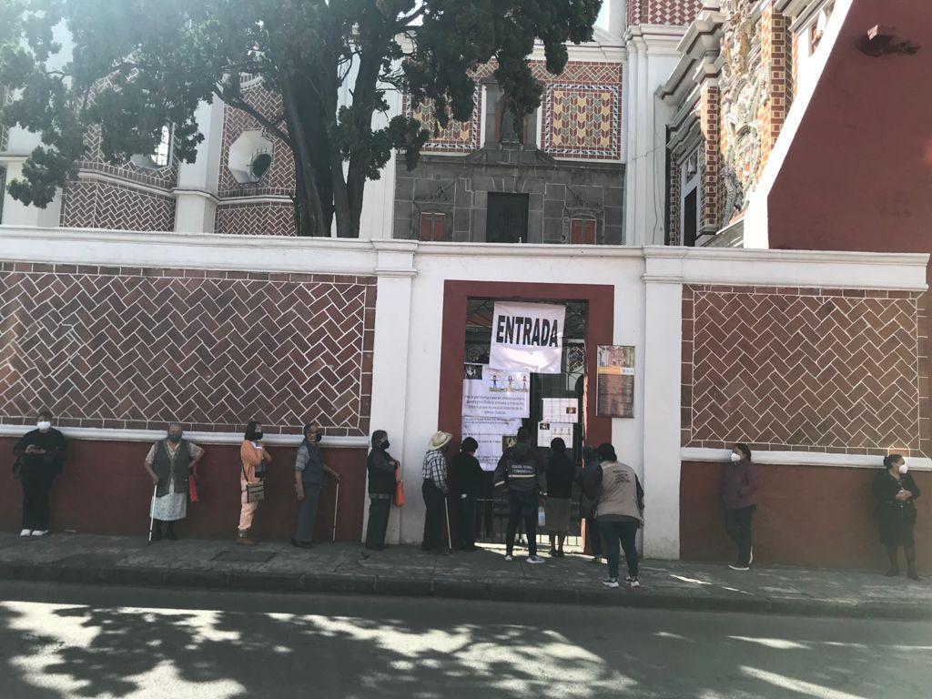 Gente formada esperando poder entrar a la iglesia de El Carmen