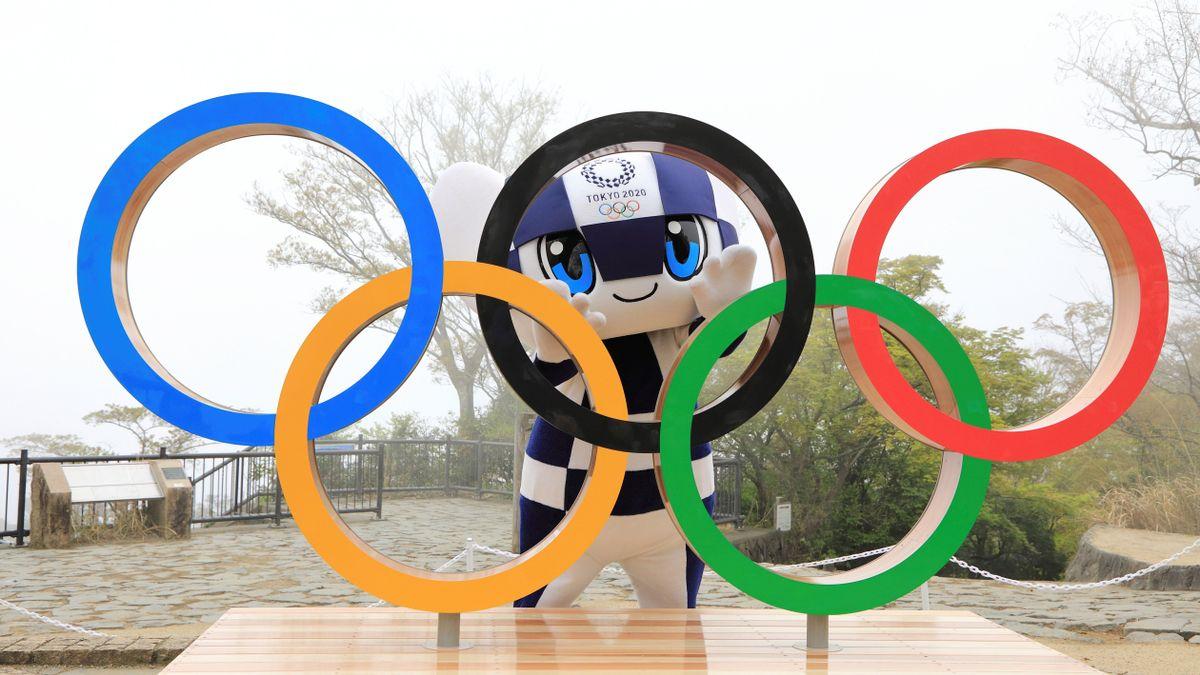 Se ven los cinco aros de los juegos olimpicos y en el medio de uno la mascota de los juegos olimpicos tokio 2020